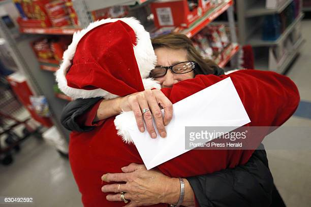 Germaine Norbert of Springvale hugs Secret Santa Maine after receiving an envelope with $100 while shopping at Family Dollar in Sanford