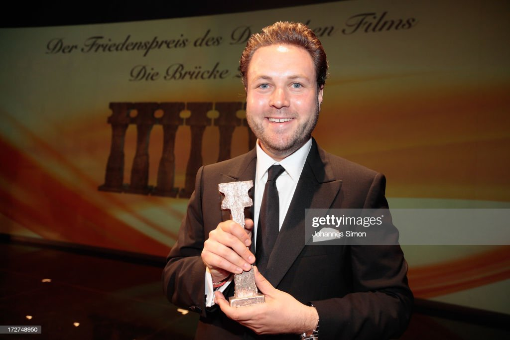 German actor and award winner Daniel Harrich poses with the award trophy after the Bernhard Wicki Award ceremony at Munich film festival on July 4, 2013 in Munich, Germany.
