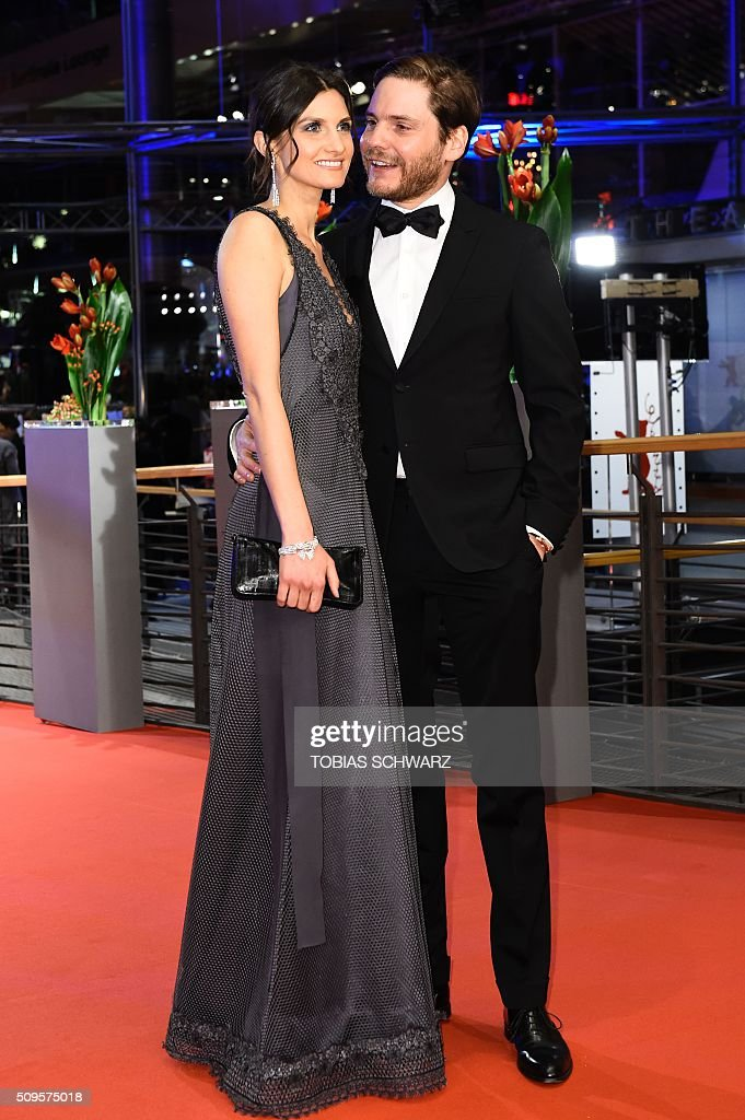 German actor Daniel Bruehl (R) and his girl-friend Felicitas Romboldt pose upon arrival for the film 'Hail, Caesar!' screening as opening film of the 66th Berlinale Film Festival in Berlin on February 11, 2016. / AFP / TOBIAS SCHWARZ