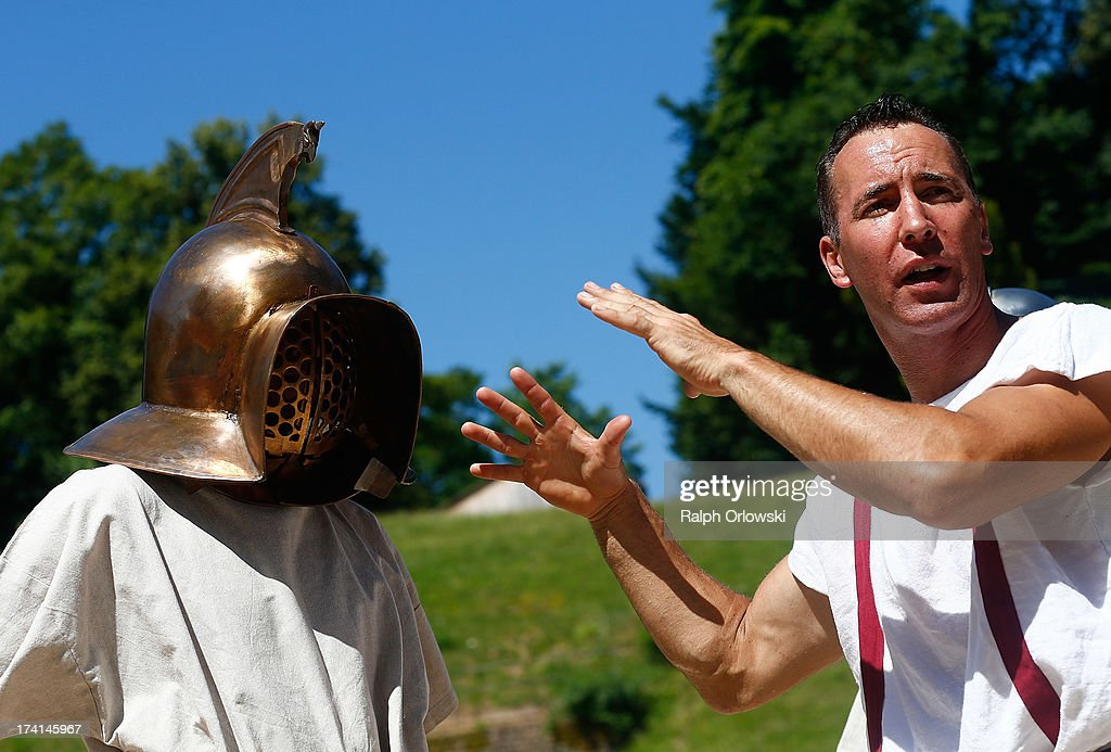 German actor Jan Krueger (R) explains the use of a helmet during his one-day course at the Gladiator School in the Roman-era amphitheater on July 20, 2013 in Trier, Germany. The Gladiator School, launched by Krueger in 2011, seeks to teach not only the fighting skills of the gladiators of ancient Rome, but also the philosophy behind the gladiator ethos. The school offers a variety of classes, including one and three-day courses.