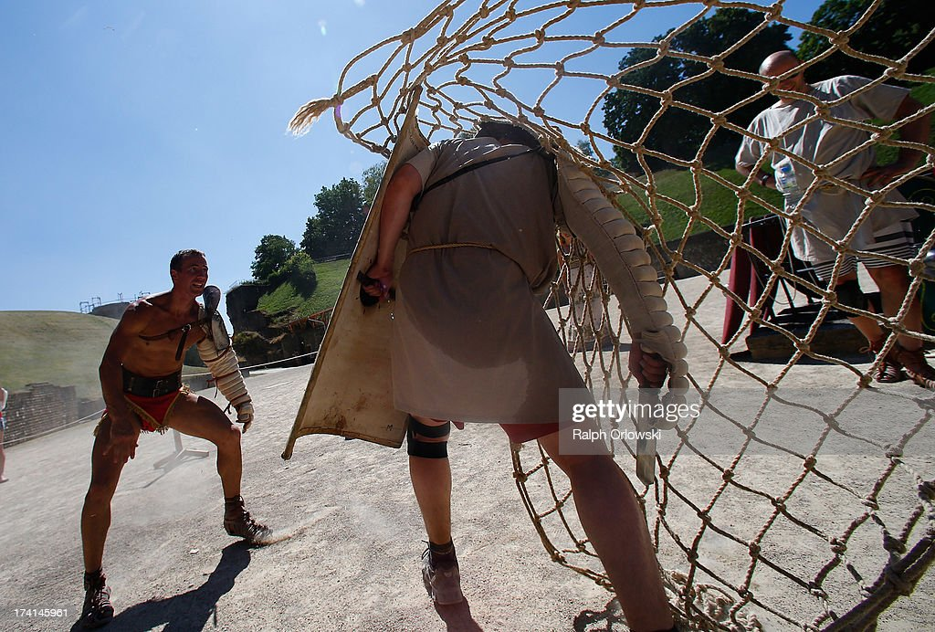 German actor Jan Krueger (L) throws a net over a participant of a one-day course in fighting at the Gladiator School in the Roman-era amphitheater on July 20, 2013 in Trier, Germany. The Gladiator School, launched by Krueger in 2011, seeks to teach not only the fighting skills of the gladiators of ancient Rome, but also the philosophy behind the gladiator ethos. The school offers a variety of classes, including one and three-day courses.