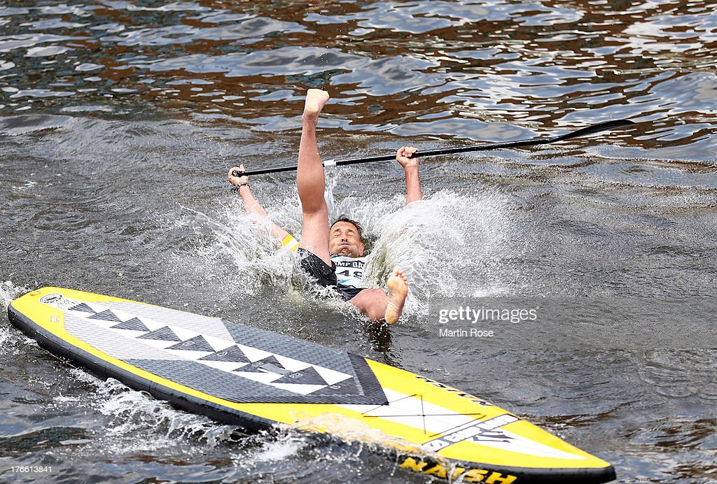 German Actor Mark keller falls ino the water during the Stand Up Paddling celebrity race at Magellan Terassen on August 16, 2013 in Hamburg, Germany.