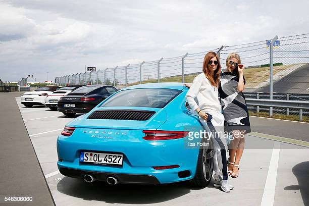 German actress Claudia Eisinger and german actress Julia Dietze on the side of a Porsche 911 Carrera S both wearing a total look from the Porsche...