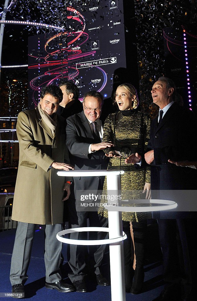 German actress Diane Kruger (2nd R), next to Paris' mayor Bertrand Delanoe (R), Jean-Noël Reinhardt (2nd L) and Pierre Lellouch (L), switchs on the Christmas lights on the Champs-Elysees avenue in Paris, on November 21, 2012.