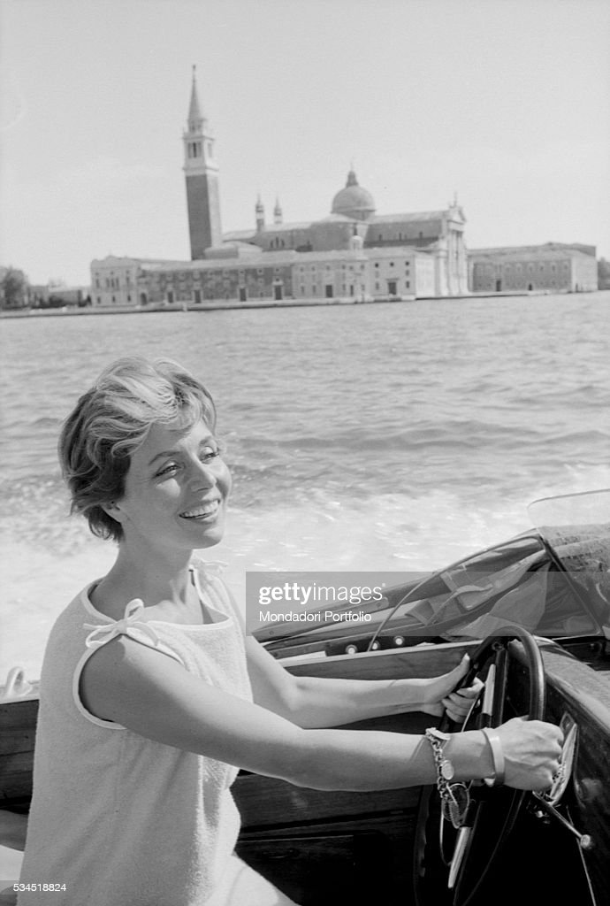 German actress Sonja Ziemann driving a motorboat during the 19th Venice International Film Festival. In the background, the astonishing architectures of Saint Mark's square. Venice, August 1958