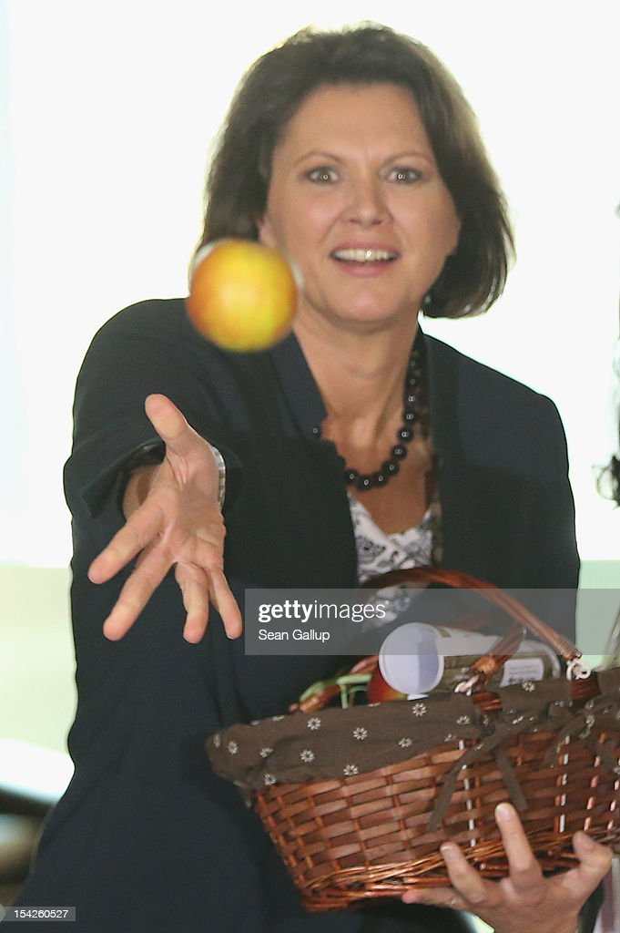 German Agriculture and Consumer Protection Minister <a gi-track='captionPersonalityLinkClicked' href=/galleries/search?phrase=Ilse+Aigner&family=editorial&specificpeople=2158567 ng-click='$event.stopPropagation()'>Ilse Aigner</a> tosses an apple to photographers after receiving a bsket from regional Harvest Queens prior to the weekly German government cabinet meeting on October 17, 2012 in Berlin, Germany. Six Harvest Queens from apple-producing regions across Germany presented cabinet members with gifts from this year's apple harvest.