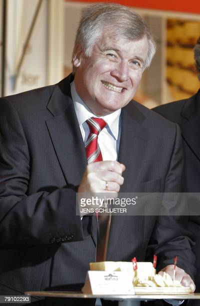 German Agriculture minister Horst Seehofer tries some Swiss cheese on the stand of Switzerland this year's honorary guest 18 January 2008 as he tours...