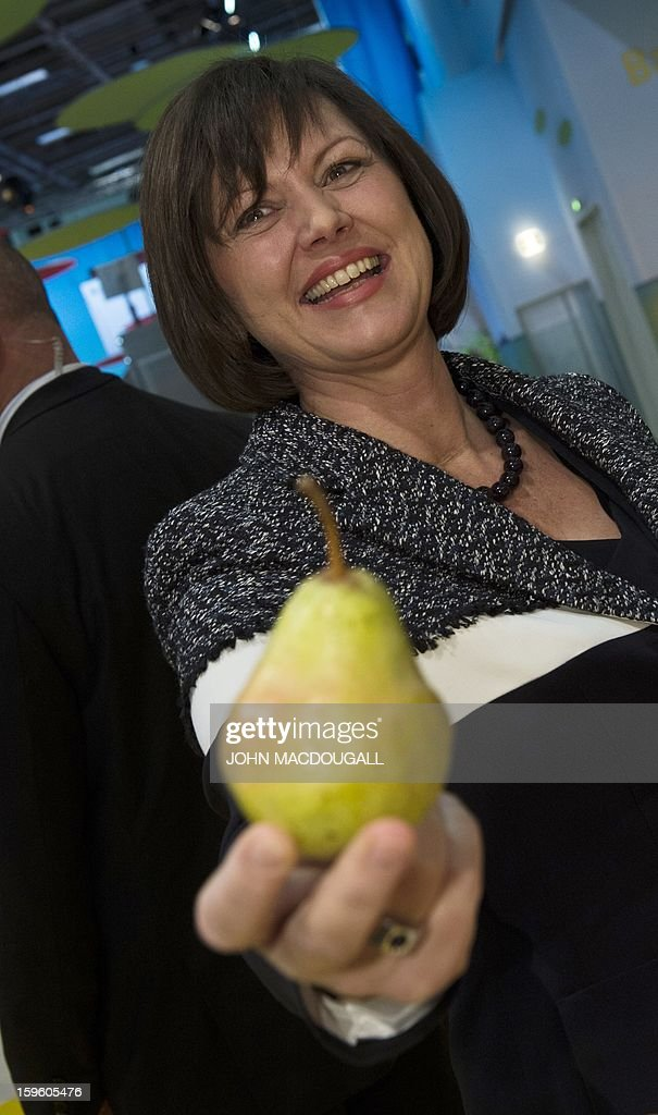 German Agriculture Minister Ilse Aigner holds up a pear as she tours the German agriculture ministry's hall at the Gruene Woche (Green Week ) Agricultural Fair in Berlin on January 17, 2013. AFP PHOTO / JOHN MACDOUGALL