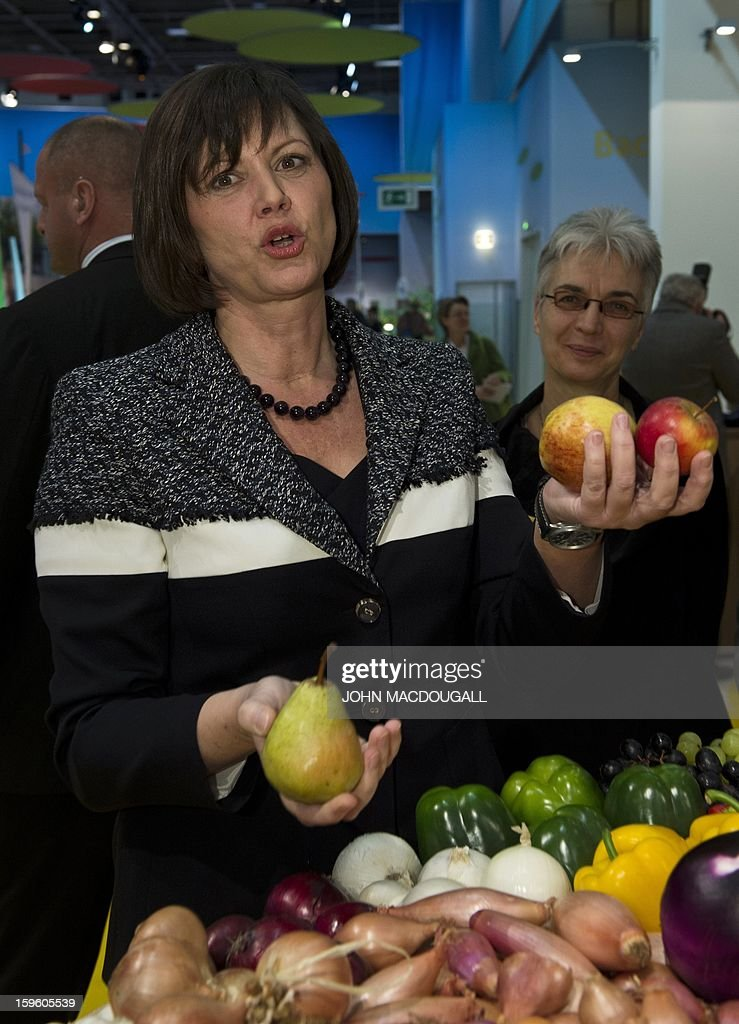 German Agriculture Minister Ilse Aigner picks up a pear and apples at a fruit and vegetable stand as she tours the German agriculture ministry's hall at the Gruene Woche Agricultural Fair in Berlin on January 17, 2013.