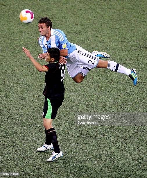 German Alejo Pezzella of Argentina climbs above Oribe Peralta in action during the Men's Football Gold Medal match between Argentina and Mexico...