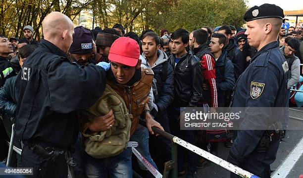 A German and an Austrian police officer control Migrants wait ahead they cross the AustrianGerman border near the Bavarian town of Passau southern...