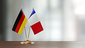 German and French flag pair on desk over defocused background. Horizontal composition with copy space and selective focus.