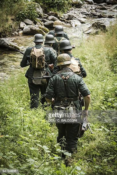 German armed forces on patrol along a stream in search of partisans Italian front 1944 Second World War 20th century Historical reenactment