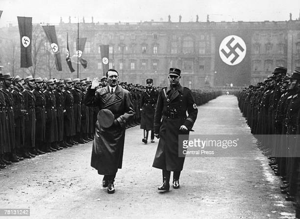 German army officer Viktor Lutze accompanies German leader Adolf Hitler on a review of the army in Berlin to commemorate the third anniversary of...