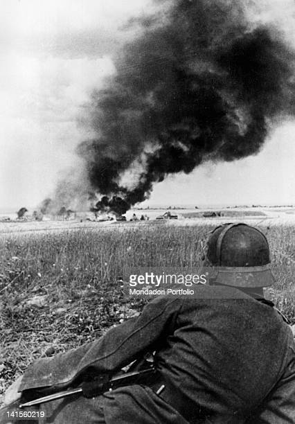 German army soldier watches the fire in a lower Ukrainian village from faroff Ukraine September 1941
