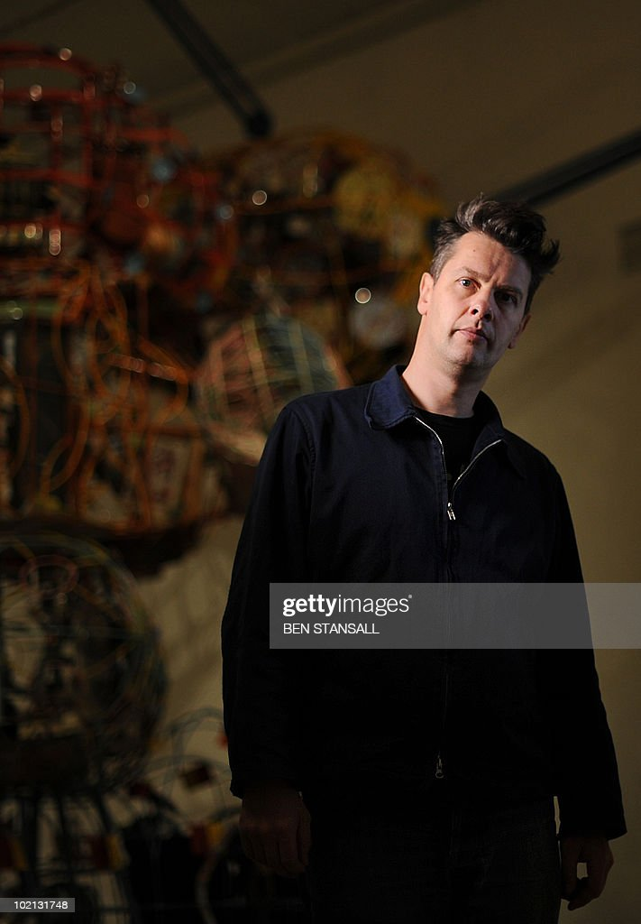 German artist John Bock poses for pictures infront of his art installation entitled 'Curve-Vehicle incl. pi-Man-(.)' in London, on June 9, 2010. The first major UK commission for the internationally acclaimed artist, Bock is renowned for his humorous, eccentric and chaotic interventions that combine sculpture, film and his trademark performances known as 'lectures'.