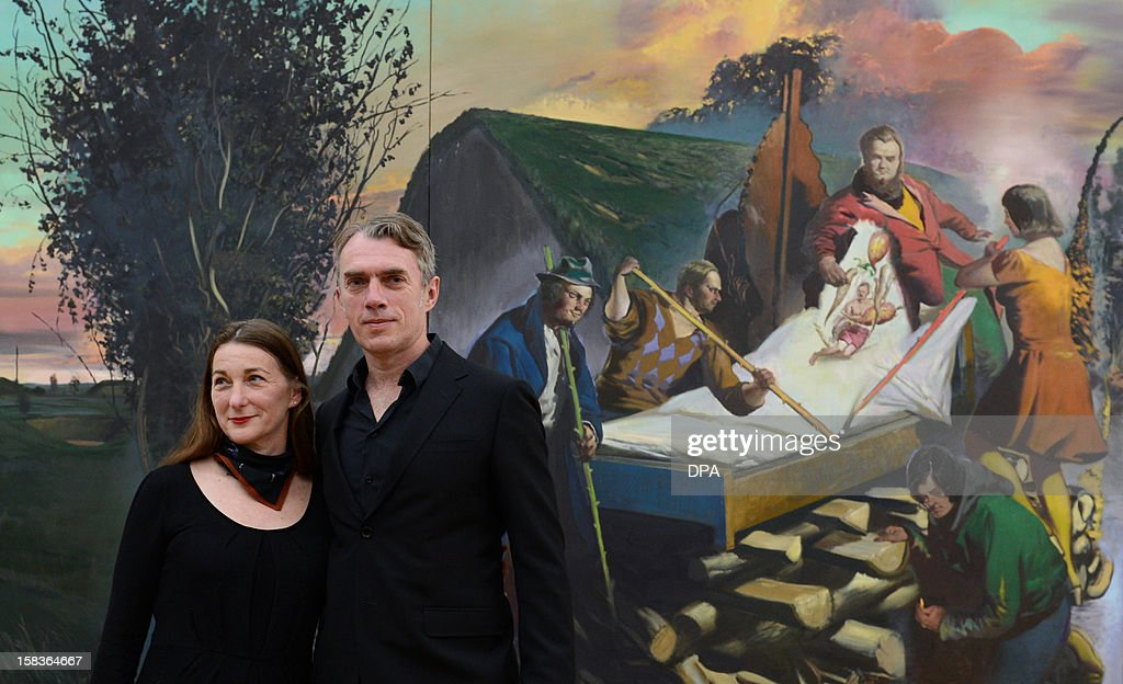 German artists Neo Rauch (R) and his wife Rosa Loy pose in front of Rauch's work 'Der boese Kranke' (2012) during a preview of a double exhibition of the couple at the Kunstsammlungen Chemnitz museum in Chemnitz, eastern Germany, on December 14, 2012. From December 16, 2012 to February 10, 2013, the museum will present simultaneously the show 'Gravitation' with works by Rosa Loy and the show 'Abwaegung' (consideration) with works by Neo Rauch.