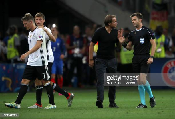German assistant manager Thomas Schneider appeals the decision of match referee Nicola Rizzoli to give a yellow card to Bastian Schweinsteiger