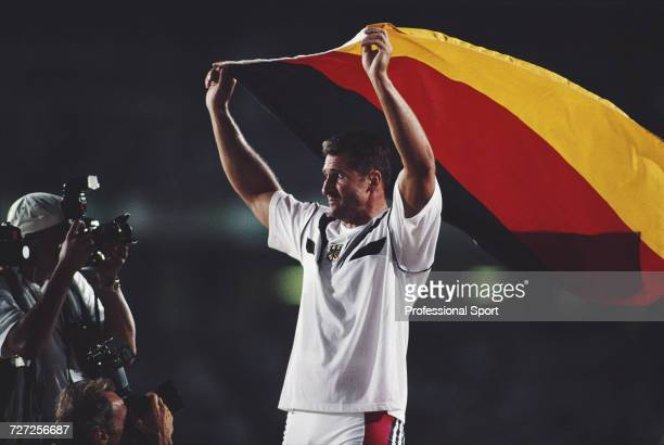 German athlete Lars Riedel celebrates with the national flag of Germany after finishing in first place to win the gold medal in the Men's discus...
