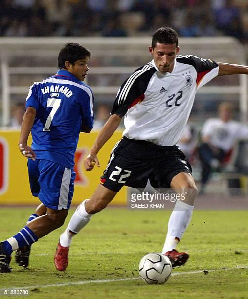 German attacker Kevin Kuranji after dodging Thai defender Rungroj Sawangsri marks first goal in the first half of a friendly match in Bangkok 21...