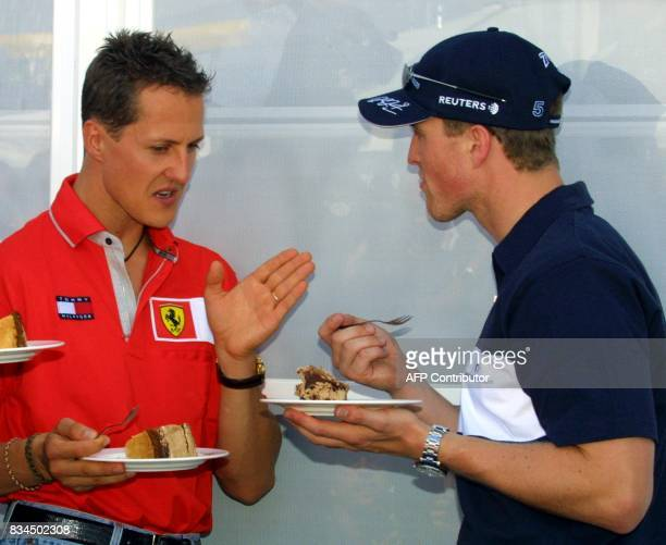 German BMWWilliams driver Ralf Schumacher talks with his brother Ferrari driver Michael during his birthday celebration in the paddock of the...