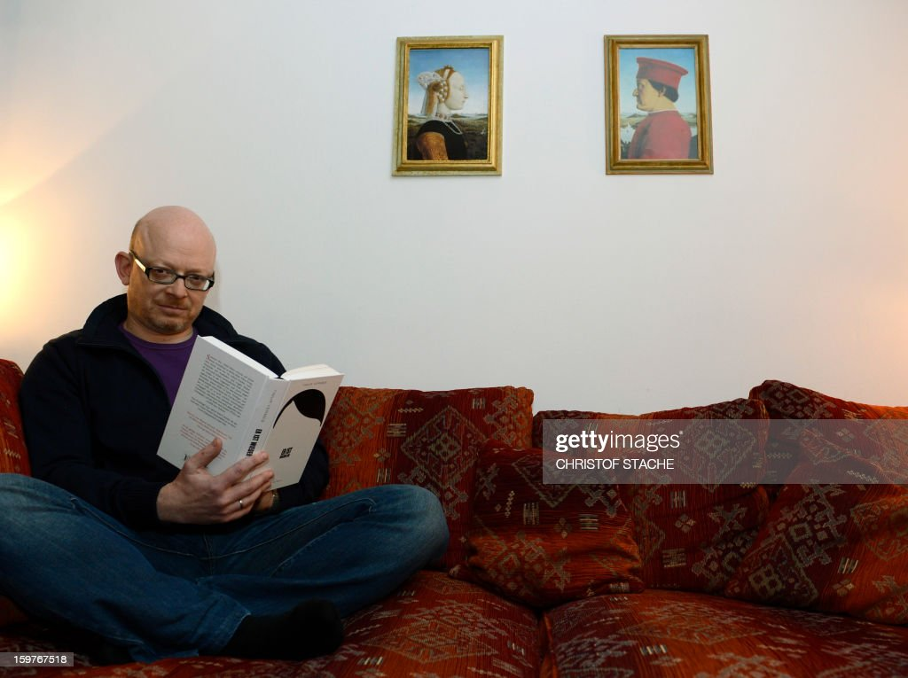 PASQUET - German book writer Timur Vermes poses with his new book 'Er ist wieder da' in his flat in Munich, southern Germany, on January 18, 2013. What would happen if Hitler would be alive today? The satire 'Er ist wieder da' envisions Hitler living in the twenty-first century in Berlin.