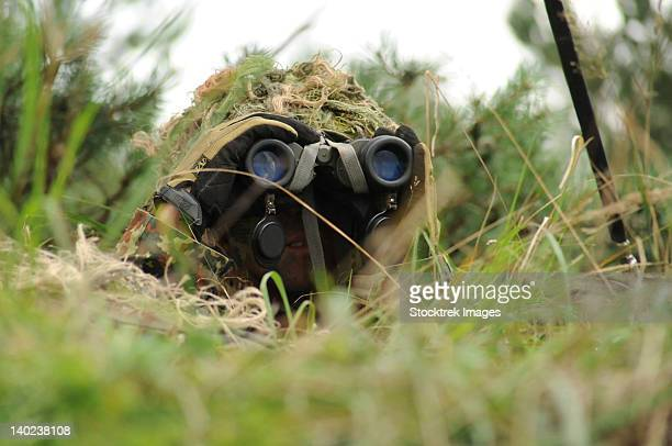 A German Bundeswehr soldier camouflages himself to blend into his surroundings.