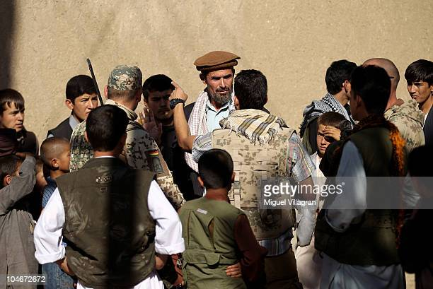 German Bundeswehr soldiers and their interpreter talk to locals during a patrol on October 2 2010 in Feyzabad Afghanistan Germany has more than 4500...