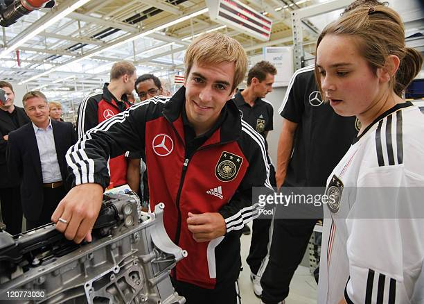 German captain Philipp Lahm inspects a machine during a visit of the German national football team at the MercedesBenz engine factory Bad Cannstatt...