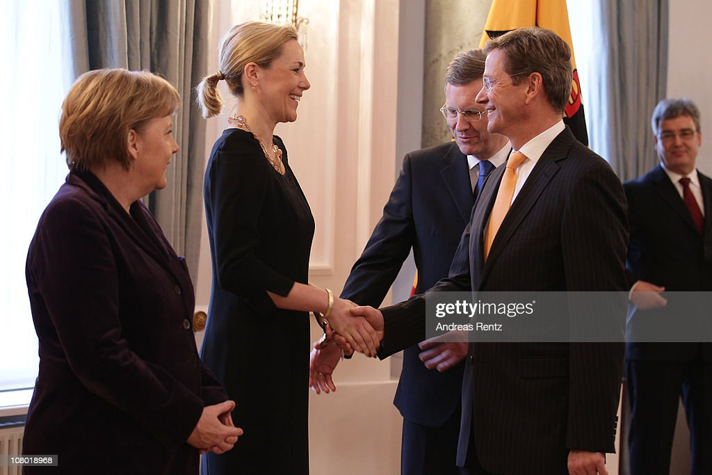 German Chacellor <a gi-track='captionPersonalityLinkClicked' href=/galleries/search?phrase=Angela+Merkel&family=editorial&specificpeople=202161 ng-click='$event.stopPropagation()'>Angela Merkel</a> (L) looks on as German First Lady <a gi-track='captionPersonalityLinkClicked' href=/galleries/search?phrase=Bettina+Wulff&family=editorial&specificpeople=5780590 ng-click='$event.stopPropagation()'>Bettina Wulff</a> (2nd-L) shakes hands with German Vice Chancellor and Foreign Minister <a gi-track='captionPersonalityLinkClicked' href=/galleries/search?phrase=Guido+Westerwelle&family=editorial&specificpeople=208748 ng-click='$event.stopPropagation()'>Guido Westerwelle</a> as German President <a gi-track='captionPersonalityLinkClicked' href=/galleries/search?phrase=Christian+Wulff&family=editorial&specificpeople=221618 ng-click='$event.stopPropagation()'>Christian Wulff</a> (behind) smiles during the New Year's reception at Bellevue Palace on January 13, 2011 in Berlin, Germany. German President <a gi-track='captionPersonalityLinkClicked' href=/galleries/search?phrase=Christian+Wulff&family=editorial&specificpeople=221618 ng-click='$event.stopPropagation()'>Christian Wulff</a> invites guests from all groups of the society for the annual New Year's reception.