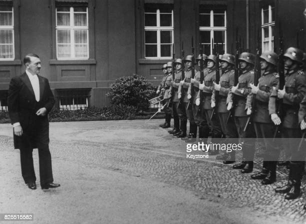 German Chancellor Adolf Hitler inspects a guard of honour in the courtyard of the Presidential Palace in Berlin Germany after a reception 27th...