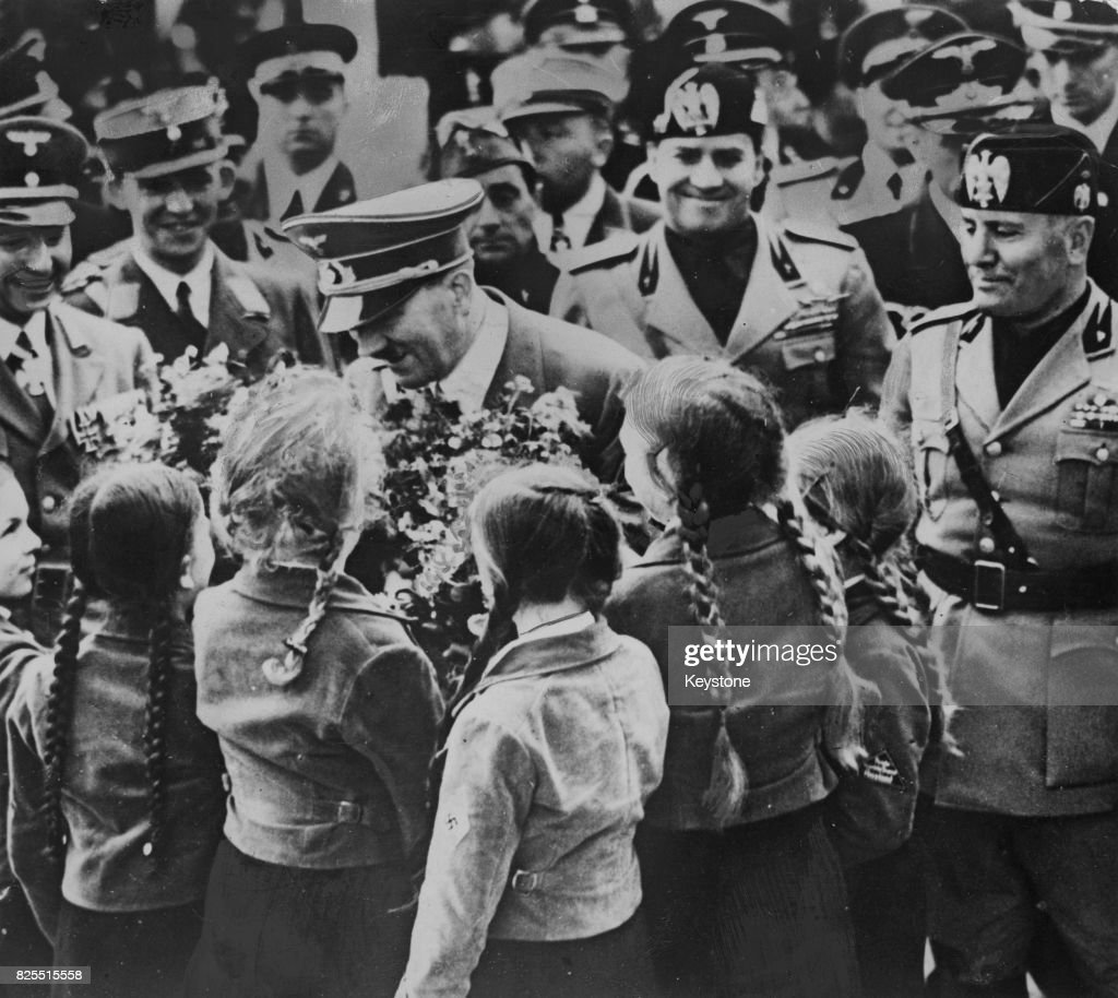 German Chancellor Adolf Hitler (1889 - 1945) receives a bouquet from a group of girls upon his arrival at the old Roman Forum in Rome, Italy, with Italian Prime Minister Benito Mussolini (right), 5th May 1938. Hitler is there to address Germans living in Italy.