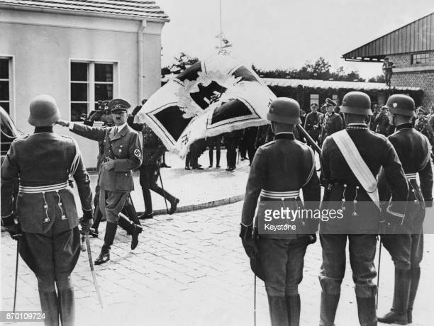 German Chancellor Adolf Hitler salutes the flag whilst inspecting a guard of honour outside the station at Gross Born Pomerania August 1938 He is...