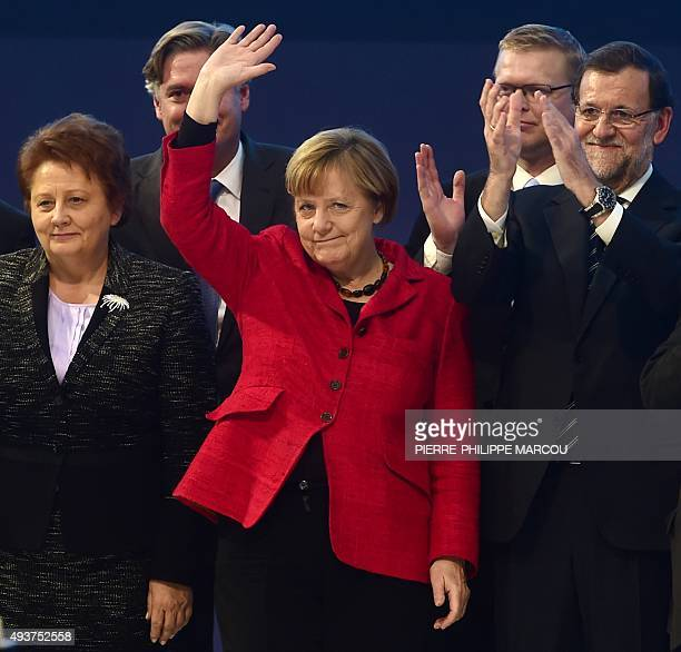 German Chancellor and CDU federal chairwoman Angela Merkel waves flanked by Latvia's Prime Minister Laimdota Straujuma Spanish Prime Minister Mariano...