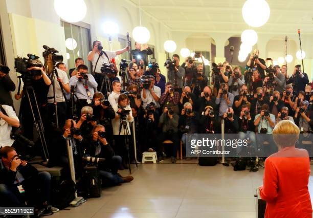 German Chancellor and CDU party leader Angela Merkel as photographers and cameramen crowd the polling station on September 24 2017 in Berlin during...