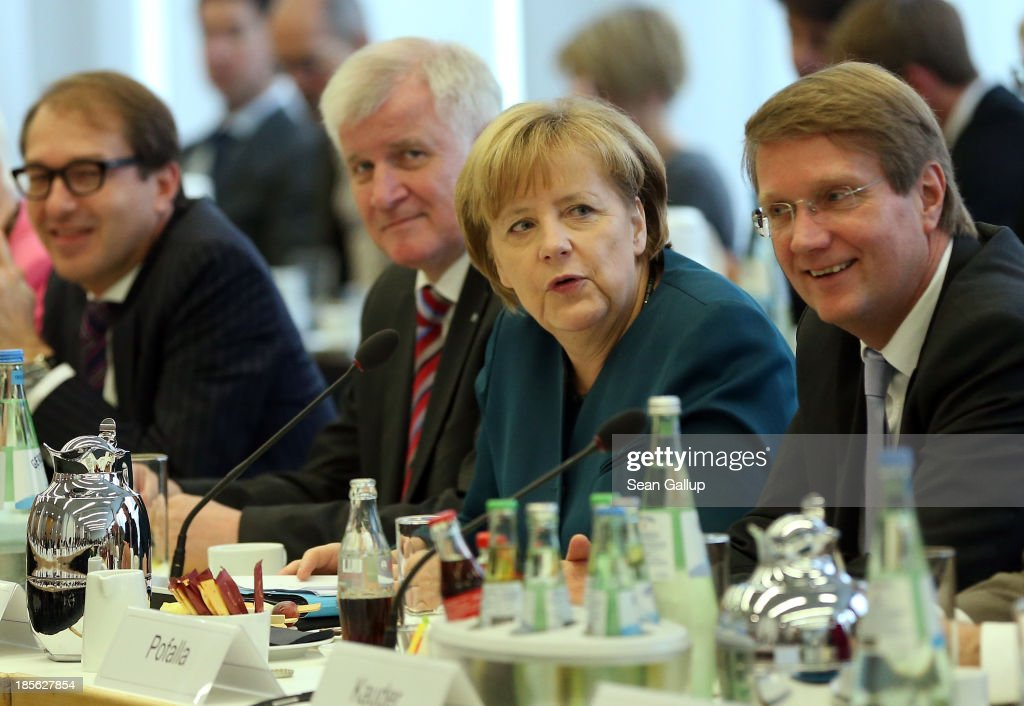 German Chancellor and Chairwoman of German Christian Democrats (CDU) <a gi-track='captionPersonalityLinkClicked' href=/galleries/search?phrase=Angela+Merkel&family=editorial&specificpeople=202161 ng-click='$event.stopPropagation()'>Angela Merkel</a> and Chairman of the Bavarian Christian Democrats (CSU) <a gi-track='captionPersonalityLinkClicked' href=/galleries/search?phrase=Horst+Seehofer&family=editorial&specificpeople=4273631 ng-click='$event.stopPropagation()'>Horst Seehofer</a> (2nd from L) sit down for the first day of coalition negotations with the German Social Democrats (SPD) at CDU headquarters on October 23, 2013 in Berlin, Germany. The CDU/CSU and SPD are meeting for the first day of negotiations in order to create a new coalition government following recent elections in Germany.