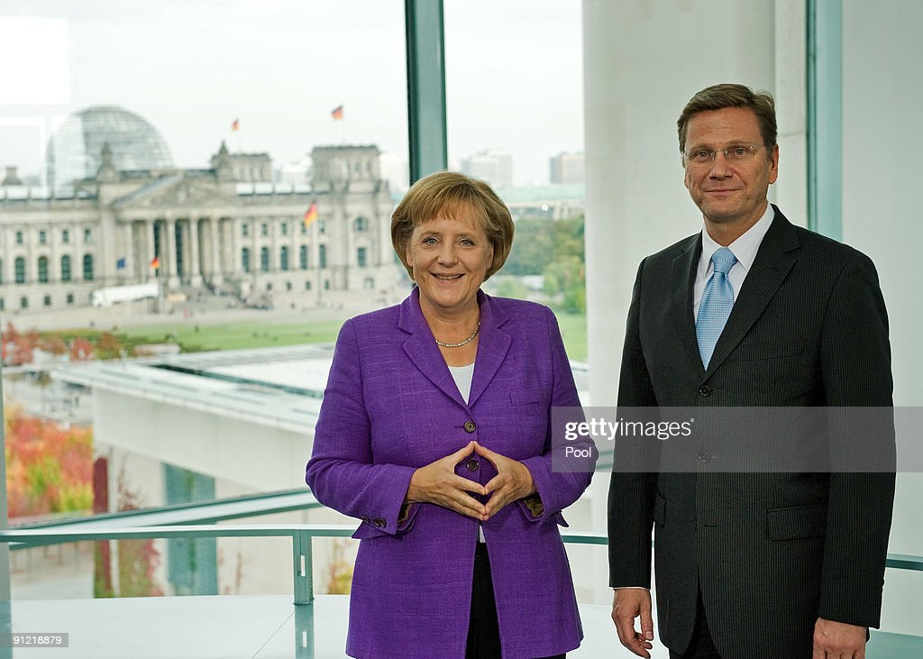 German Chancellor and Chairwoman of the Christian Democratic Union (CDU) political party <a gi-track='captionPersonalityLinkClicked' href=/galleries/search?phrase=Angela+Merkel&family=editorial&specificpeople=202161 ng-click='$event.stopPropagation()'>Angela Merkel</a> (L) and <a gi-track='captionPersonalityLinkClicked' href=/galleries/search?phrase=Guido+Westerwelle&family=editorial&specificpeople=208748 ng-click='$event.stopPropagation()'>Guido Westerwelle</a>, party leader of the Free Democratic Party (FDP) pose for the media after first talks at the Chancellery on September 28, 2009 in Berlin, Germany. The CDU finished well ahead of its rivals and will likely form a coalition government with the business-oriented German Free Democrats (FDP).