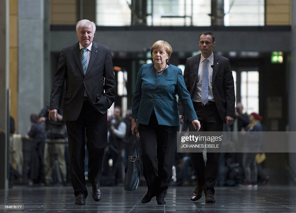 German Chancellor and chairwoman of the Christian Democrats (CDU) Angela Merkel and Prime Minister of German State of Bavaria, Horst Seehofer (CSU) are on their way to a meeting of the CDU/CSU party before the 2nd round of exploratory talks with the Green party on forming a coalition government in Berlin on October 15, 2013. The exploratory talks with the left-leaning ecologist party are part of Merkel's hunt for a governing partner after her conservatives won September 22 elections but fell short of a ruling majority.
