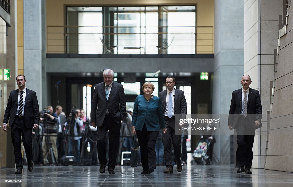 German Chancellor and chairwoman of the Christian Democrats (CDU) Angela Merkel (C) and Prime Minister of German State of Bavaria, Horst Seehofer (CSU, L) are on their way to a meeting of the CDU/CSU party before the 2nd round of exploratory talks with the Green party on forming a coalition government in Berlin on October 15, 2013. The exploratory talks with the left-leaning ecologist party are part of Merkel's hunt for a governing partner after her conservatives won September 22 elections but fell short of a ruling majority.