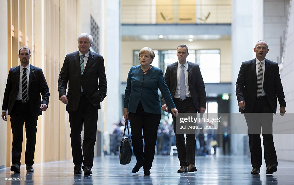 German Chancellor and chairwoman of the Christian Democrats (CDU) Angela Merkel (C) and Prime Minister of German State of Bavaria, Horst Seehofer (CSU, 2nd L) are on their way to a meeting of the CDU/CSU party before the 2nd round of exploratory talks with the Green party on forming a coalition government in Berlin on October 15, 2013. The exploratory talks with the left-leaning ecologist party are part of Merkel's hunt for a governing partner after her conservatives won September 22 elections but fell short of a ruling majority.