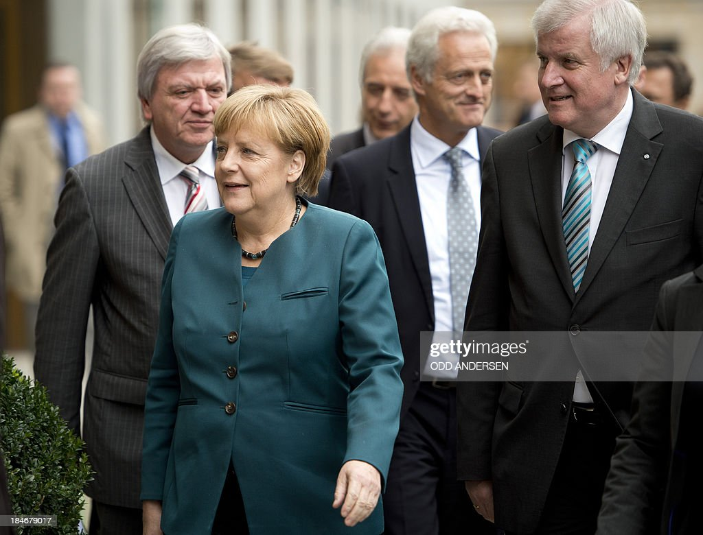 German Chancellor and chairwoman of the Christian Democrats (CDU) Angela Merkel (2nd L) and Prime Minister of German State of Bavaria, Horst Seehofer (CSU, R) are on their way to the 2nd round of exploratory talks with the Green party on forming a coalition government in Berlin on October 15, 2013. The exploratory talks with the left-leaning ecologist party are part of Merkel's hunt for a governing partner after her conservatives won September 22 elections but fell short of a ruling majority.