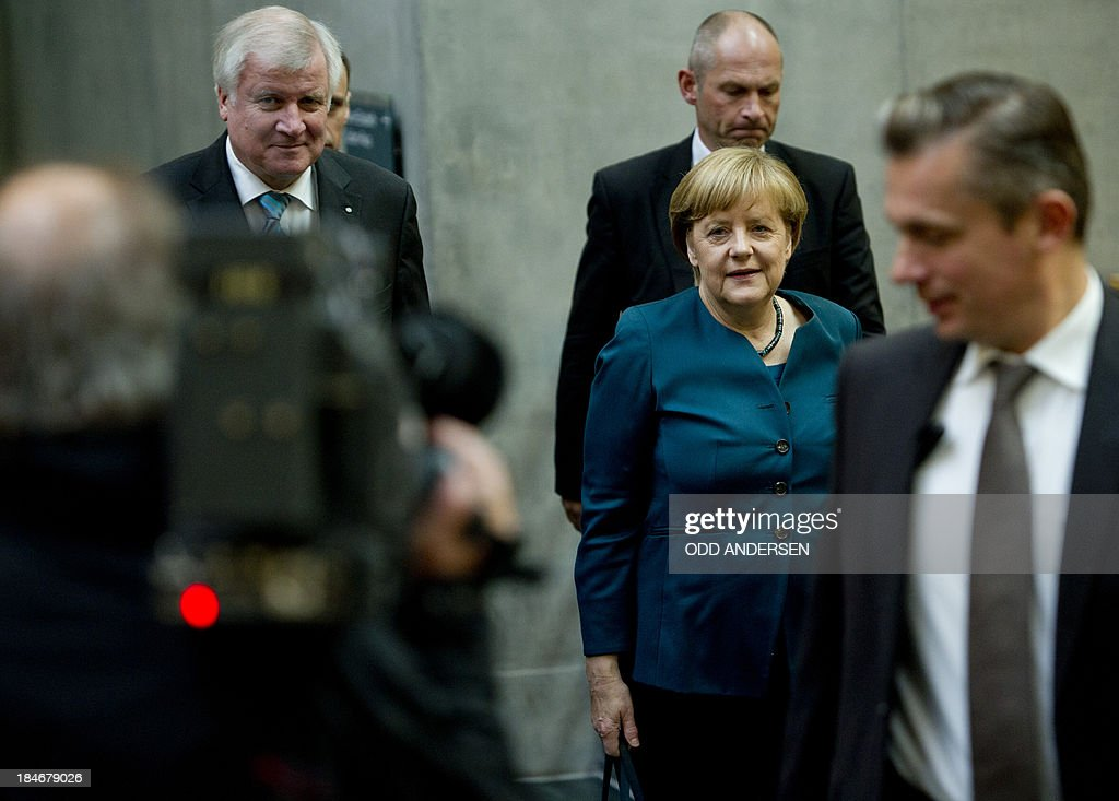 German Chancellor and chairwoman of the Christian Democrats (CDU) Angela Merkel (2nd R) and Prime Minister of German State of Bavaria, Horst Seehofer (CSU, L) are on their way to the 2nd round of exploratory talks with the Green party on forming a coalition government in Berlin on October 15, 2013. The exploratory talks with the left-leaning ecologist party are part of Merkel's hunt for a governing partner after her conservatives won September 22 elections but fell short of a ruling majority.