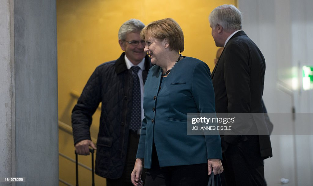 German Chancellor and chairwoman of the conservative Christian Democratic Union (CDU) Angela Merkel and Horst Seehofer (R), State Premier of Bavaria and leader of the Christian Social Union (CSU), arrive for a meeting ahead of talks with members of the Green party on October 15, 2013 in Berlin. The exploratory talks with the left-leaning ecologist party are part of German Chancellor Angela Merkel's hunt for a governing partner after her conservatives won September 22 elections but fell short of a ruling majority.