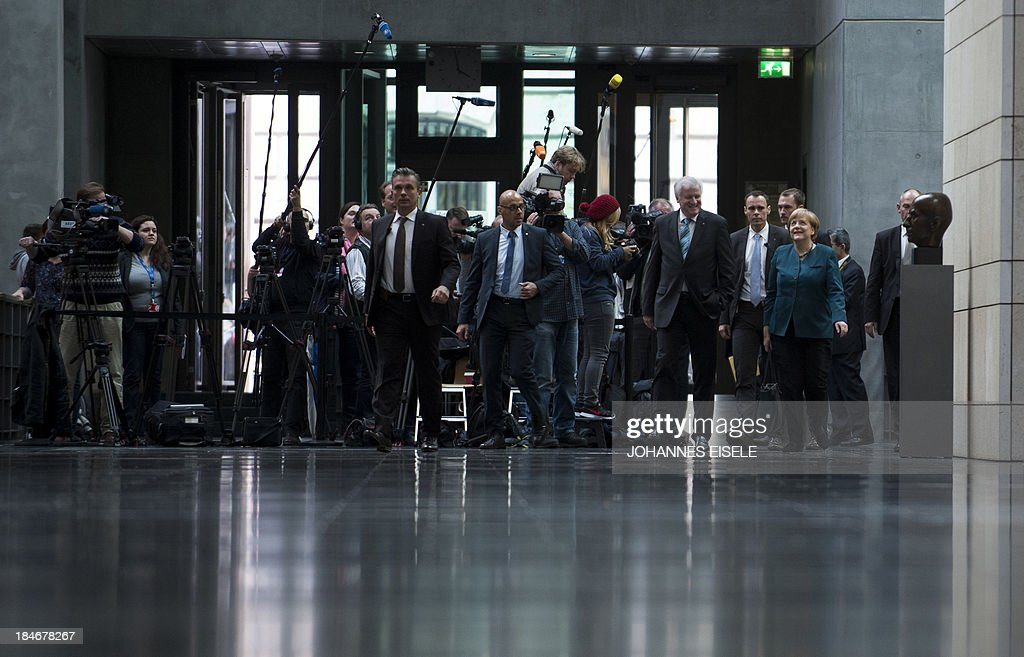 German Chancellor and chairwoman of the conservative Christian Democratic Union (CDU) Angela Merkel (R) and Horst Seehofer (on L beside her), State Premier of Bavaria and leader of the Christian Social Union (CSU), arrive for a meeting ahead of talks with members of the Green party on October 15, 2013 in Berlin. The exploratory talks with the left-leaning ecologist party are part of German Chancellor Angela Merkel's hunt for a governing partner after her conservatives won September 22 elections but fell short of a ruling majority.