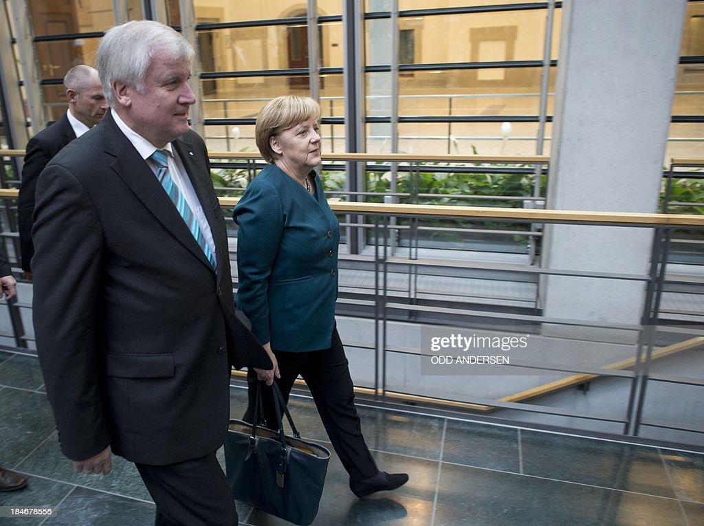 German Chancellor and chairwoman of the conservative Christian Democratic Union (CDU) Angela Merkel and Horst Seehofer (R), State Premier of Bavaria and leader of the Christian Social Union (CSU), arrive for a meeting ahead of talks with members of the Green party on October 15, 2013 in Berlin. The exploratory talks with the left-leaning ecologist party are part of Merkel's hunt for a governing partner after her conservatives won September 22 elections but fell short of a ruling majority.