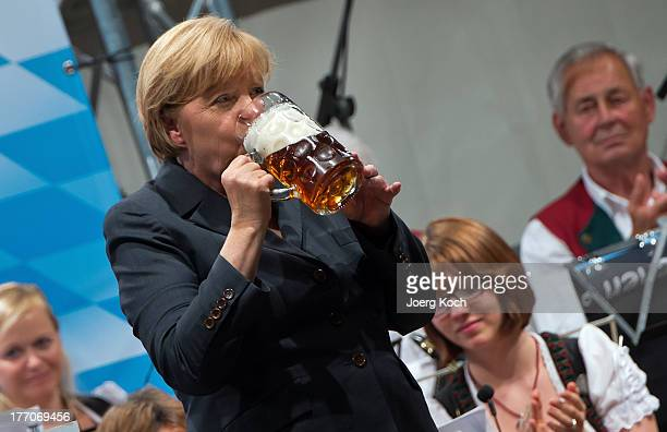German Chancellor and Chairwoman of the German Christian Democrats Angela Merkel drinks a beer after speaking at an election campaign stop in a fest...