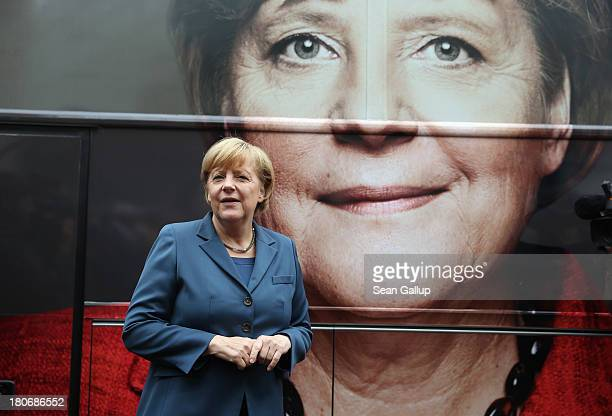 German Chancellor and Chairwoman of the German Christian Democrats Angela Merkel poses in front of a CDU elections campaign bus outside CDU...
