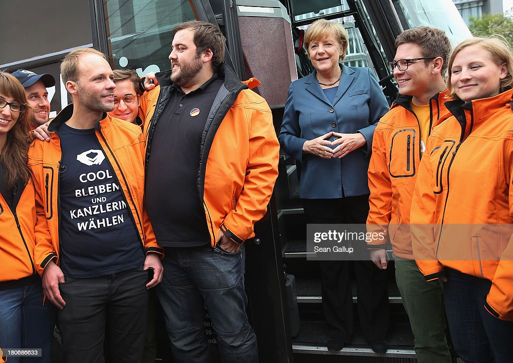 German Chancellor and Chairwoman of the German Christian Democrats (CDU) <a gi-track='captionPersonalityLinkClicked' href=/galleries/search?phrase=Angela+Merkel&family=editorial&specificpeople=202161 ng-click='$event.stopPropagation()'>Angela Merkel</a> stands among CDU campaign volunteers while standing on the doorstep of a CDU elections campaign bus outside CDU headquarters on September 16, 2013 in Berlin, Germany. Germany faces federal elections on September 22 and so far the CDU has a strong lead in polls over the opposition.