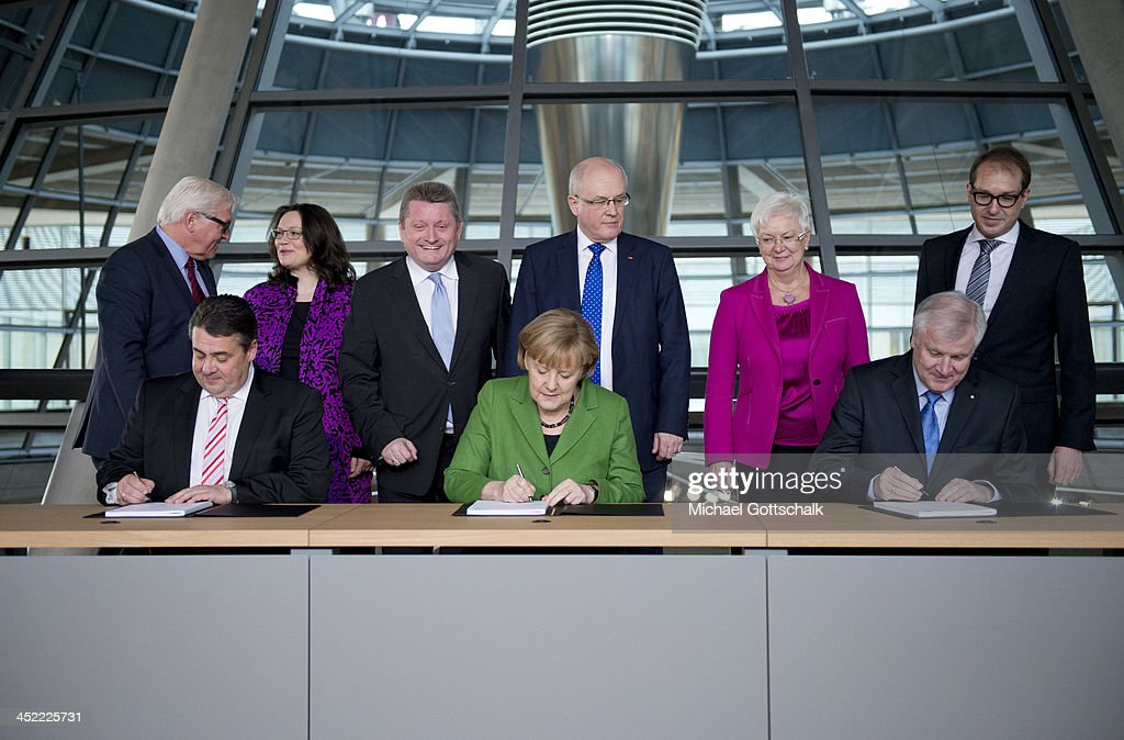 German Chancellor and Chairwoman of the German Christian Democrats (CDU) <a gi-track='captionPersonalityLinkClicked' href=/galleries/search?phrase=Angela+Merkel&family=editorial&specificpeople=202161 ng-click='$event.stopPropagation()'>Angela Merkel</a> (M), Chairman of the Bavarian Christian Democrats (CSU) <a gi-track='captionPersonalityLinkClicked' href=/galleries/search?phrase=Horst+Seehofer&family=editorial&specificpeople=4273631 ng-click='$event.stopPropagation()'>Horst Seehofer</a> (R) and Chairman of the German Social Democrats (SPD) <a gi-track='captionPersonalityLinkClicked' href=/galleries/search?phrase=Sigmar+Gabriel&family=editorial&specificpeople=543927 ng-click='$event.stopPropagation()'>Sigmar Gabriel</a> (L) sign in front of (L-R) <a gi-track='captionPersonalityLinkClicked' href=/galleries/search?phrase=Frank-Walter+Steinmeier&family=editorial&specificpeople=603500 ng-click='$event.stopPropagation()'>Frank-Walter Steinmeier</a>, head of the Bundestag faction of the SPD, Secretary General of SPD <a gi-track='captionPersonalityLinkClicked' href=/galleries/search?phrase=Andrea+Nahles&family=editorial&specificpeople=822618 ng-click='$event.stopPropagation()'>Andrea Nahles</a>, Secretary General of CDU, <a gi-track='captionPersonalityLinkClicked' href=/galleries/search?phrase=Hermann+Groehe&family=editorial&specificpeople=6400355 ng-click='$event.stopPropagation()'>Hermann Groehe</a>, <a gi-track='captionPersonalityLinkClicked' href=/galleries/search?phrase=Volker+Kauder&family=editorial&specificpeople=224968 ng-click='$event.stopPropagation()'>Volker Kauder</a>, head of the Bundestag faction of CDU/CSU, <a gi-track='captionPersonalityLinkClicked' href=/galleries/search?phrase=Gerda+Hasselfeldt&family=editorial&specificpeople=2202696 ng-click='$event.stopPropagation()'>Gerda Hasselfeldt</a>, head of the Bundestag group of CSU and Secretary General of (CSU) Alexander Dobrindt, during for the provisional signing of the new coalition contract on November 27, 2013 at the German Reichstag in Berlin, Germany. The three parties worked their way through arduous negotiations on policy issues that concluded with a 17-hour overnight session last night in order to hammer out the final details that will make a new German coalition government possible. The agreement still requires approval by party delegates, which especially in the case of the SPD is uncertain.