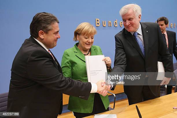 German Chancellor and Chairwoman of the German Christian Democrats Angela Merkel holds a copy of the coaliton contract as Chairman of the German...